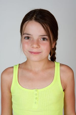 9 year old: A portrait of a nine year old girl on a neutral background.  The girl has brown eyes and long brown hair.
