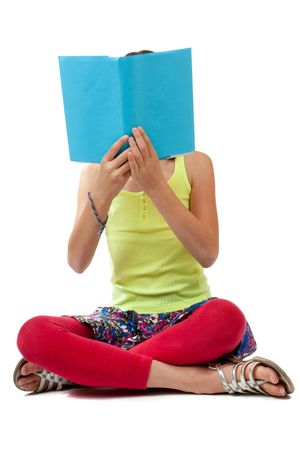 cover up: A casually dressed school age girl sits crossed legged and holds up a book with a blank blue cover up over her face.