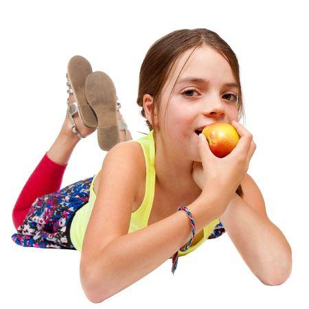 girl lying down: Una primaria de a�os a chica acostado y comer una manzana. Estudio aislado en blanco.