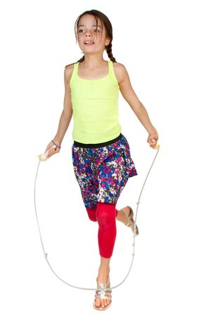 9 year old: A primary aged girl jumping over a skipping rope. Stock Photo