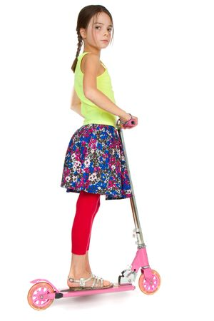 9 year old: A primary aged girl standing on a pink toy scooter. Stock Photo