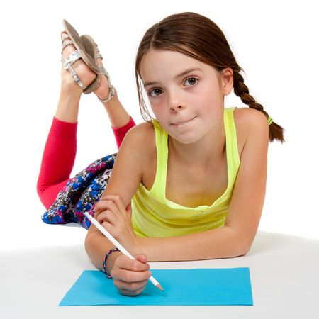 girl drawing: A primary aged girl looking thoughtful whilst drawing on some blue paper.