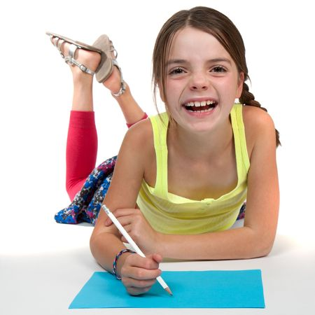 9 year old: A primary aged girl laughing whilst drawing on some blue paper. Stock Photo