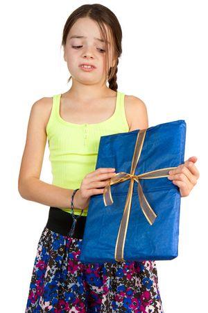 disdain: Una ni�a de edad primaria parece decepcionada a recibir un regalo de cinta envuelto.