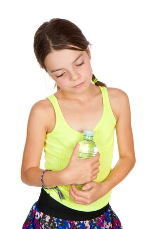 thoughful: A thoughful looking primary aged girl holding a full bottle of mineral water.