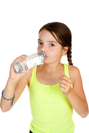 facing the camera: A primary aged girl drinking from a plastic bottle of mineral water.