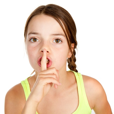 shush: A primary aged girl with her finger on her lips making a shush or shh gesture.