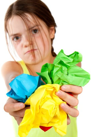 scrunched: A grumpy looking primary aged girl holding some colourful scrunched up paper close to the camera.  Differential focus on the paper.