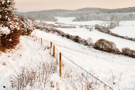 covered fields: A view over some snow covered fields at dusk.  Taken on Pewley Down in Guildford, Surrey on a snowy December evening. Stock Photo