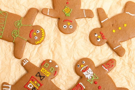 Some freshly baked home made gingerbread men arranged in a circle on some creased parchment paper (baking paper). Stock Photo - 8580706