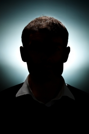 head silhouette: A portrait of a man lit with only a hair light and a background light. Stock Photo