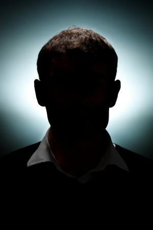 silueta humana: Un retrato de un hombre iluminado con sólo una luz de pelo y una luz de fondo. Foto de archivo