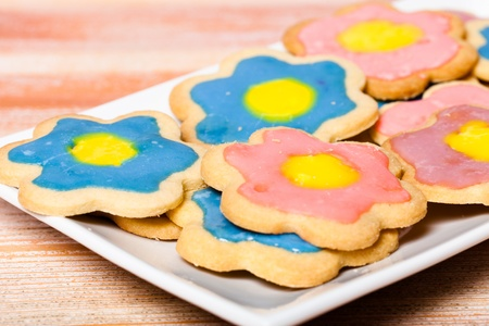 differential focus: A plate of colourful homemade star shaped biscuitscookies.  Differential focus on the front biscuit.