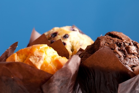 differential focus: Three muffins on a blue background.  Shallow depth of field with focus on the chocolate muffin. Stock Photo