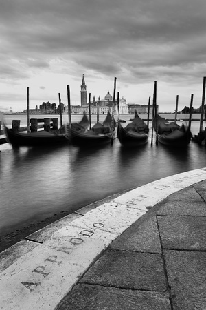 A moody black and white view of the island of San Giorgio Maggiore in Venice.  Approdo per la Strada (mooring for the street) is etched into the pavement. photo