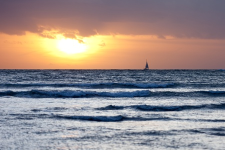 breaking wave: A sailing boat on the horizon as the sun sets over the breaking waves of the beach.  Shallow depth of field focussed on the yacht.