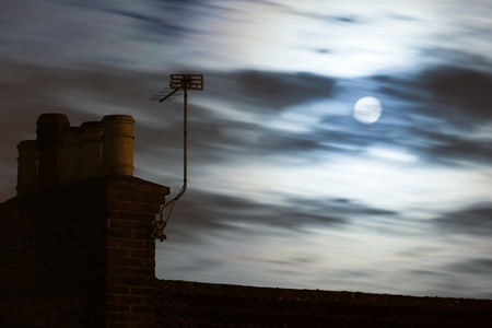 moonlit: A chimney and TV aerial on a roof top with a moonlit cloudy sky in the background.