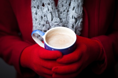 differential focus: A woman in a red coat and gloves warms her hands on a mug of hot chocolate.  Focus on the drink.