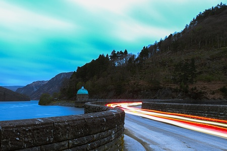 elan: A long exposure of some car lights crossing the bridge over the Cabon Coch reservoir in the Elan Valley, Wales. Stock Photo