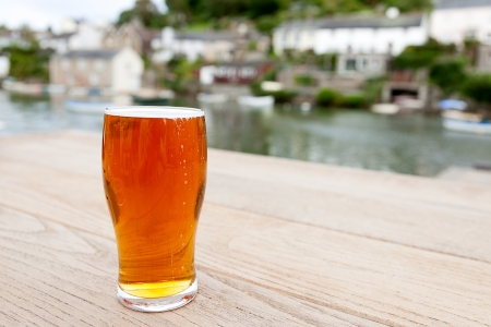 real ale: A full pint of English real ale on a wooden table outside a riverside pub   Differential focus on the glass