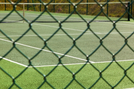 differential focus: A view of an empty tennis court through the course fence.