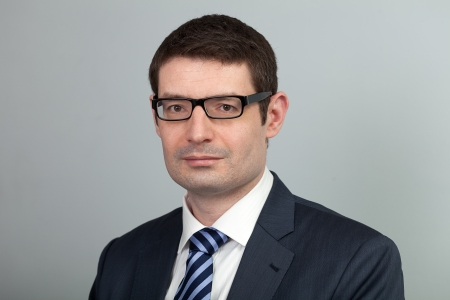 30 to 40: A head and shoulders shot of a black framed eyeglasses wearing 40 year old business man in a suit and shirt with blue tie