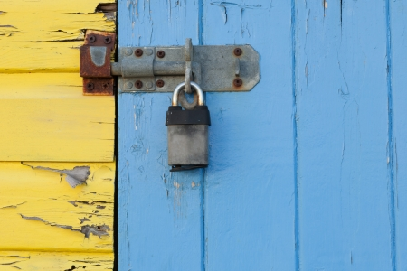 door bolt: An old and rusty padlock on a yellow and blue wooden beach hut  Stock Photo