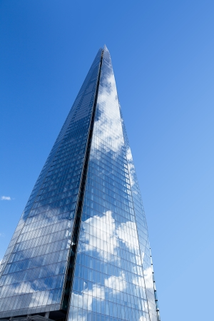 shard of glass: The Shard in London on its own against a blue sky.  Clouds are reflected in the glass panels.