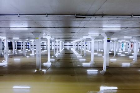 parking lot interior: About a foot of water in the lowest level of a car parking garage in Guildford, Surrey.  The ceiling lights and columns make interesting reflections. Editorial