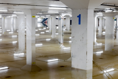 carpark: About a foot of water in the lowest level of a car parking garage in Guildford, Surrey.  The ceiling lights and columns make interesting reflections. Editorial