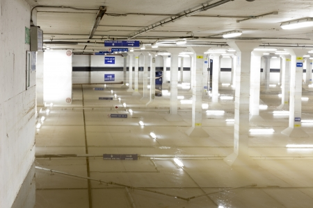 About a foot of water in the lowest level of a car parking garage in Guildford, Surrey.  The ceiling lights and columns make interesting reflections.