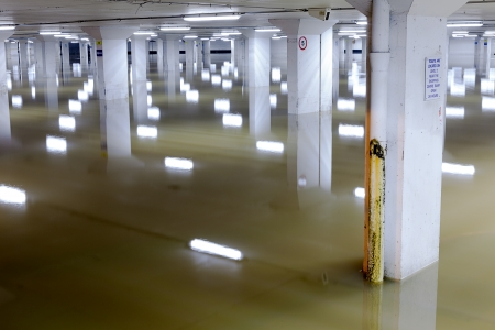 car park: About a foot of water in the lowest level of a car parking garage in Guildford, Surrey.  The ceiling lights and columns make interesting reflections. Editorial