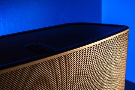 differential focus: A bookshelf speaker is lit with golden light with a blue background light.  Differential focus on the centre of the lit part of the grill. Stock Photo