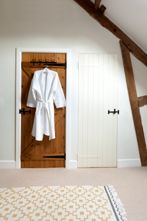 house robes: Two closed wooden doors in a loft room.  One is painted white, the other is unpainted and has a bathrobe hanging on a hook. Stock Photo