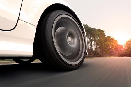Een witte auto op een weg snel rijden in de zonsondergang. Close-up op het wiel. Stockfoto