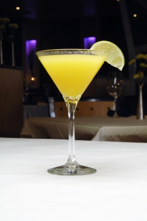 Specialty drink in a martini glass with lime served on a table in a lounge, bar or restaurant atmosphere