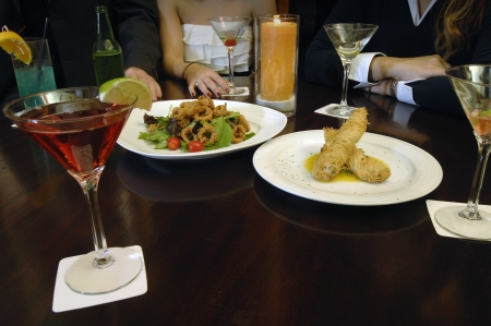 Friends enjoy Chinese, Oriental, Asian food, cuisine over cocktails, wine, beer, martinis at a restaurant