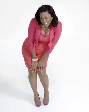 Attractive african american female in casual business attire with a happy,  successful look and demeanor  Shot froma high angle and isolated on a white background