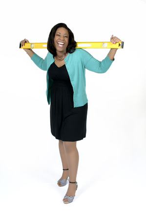 Attractive african american female in casual business attire holding home improvement, contruction tool  Isolated on a white background