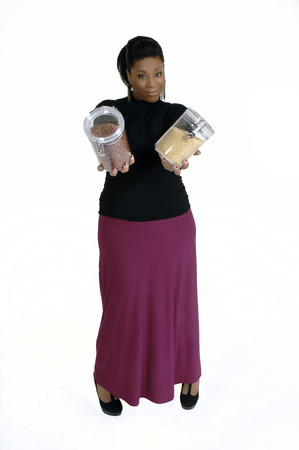 Attractive african american female in casual business attire holding jar of beans   kitchen organizational canister  Isolated on a white background