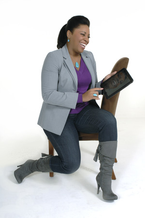Attractive, happy african american female in casual attire holding, working on a  tablet or touch pad on a wite background