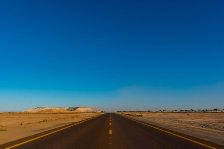 View from the center of the road to infinity in the deserted area with blue sky. Shot at summer day time. Vacation travel