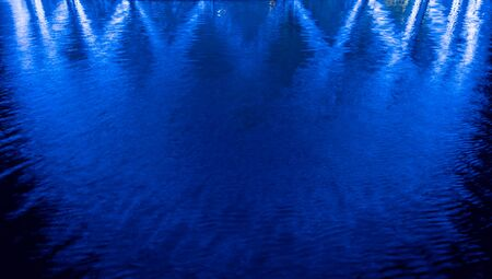 Abstract blue background, lights reflections on the water.