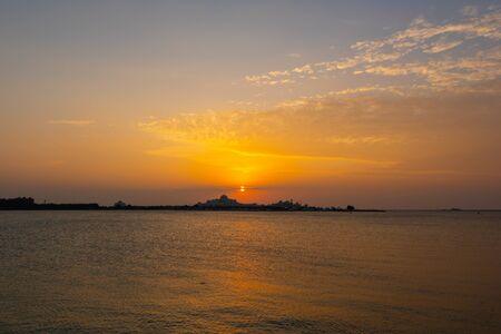 Beautiful orange sunset with lights reflections on the water 版權商用圖片