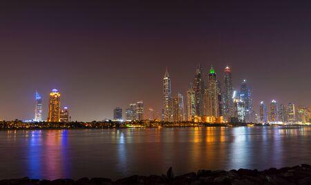 밤에 두바이 스카이라인은 물 위의 조명과 UAE의 호화로운 고층 빌딩입니다. 미래의 현대 건축.