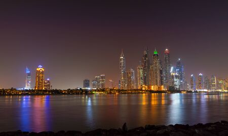 Dubai skyline at night with lights on the water and luxirious skyscrapers of UAE. Modern architecture of the future.