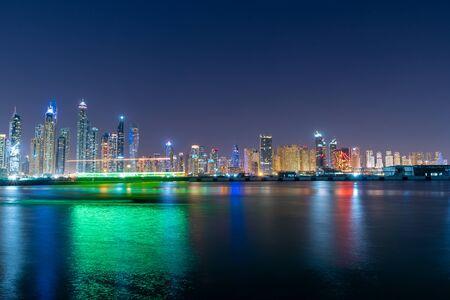 Dubai-Skyline nachts mit schönen Farben auf dem Wasser, das von den Wolkenkratzern VAE kommt. Moderne Architektur der Zukunft.