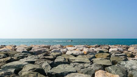 View to the blue see and sky from the rocky beach shot at bright summer day, vacation destination UAE Dubai. 版權商用圖片