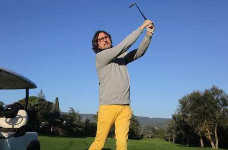 adult man in a golf iron swing