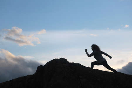 woman with running silohuette in the mountain with background sky with clouds Banque d'images